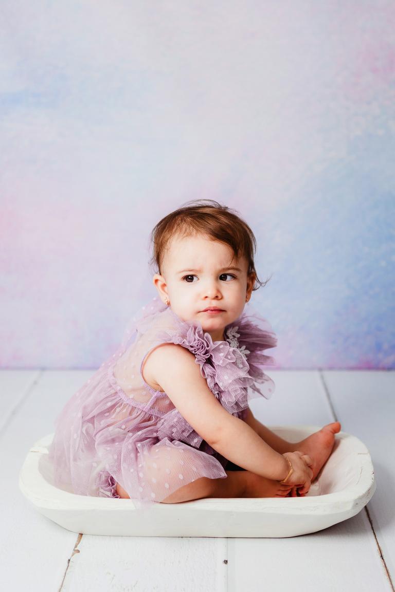 Image d'une petite fille de 17 mois en tenue violette qui regarde de côté