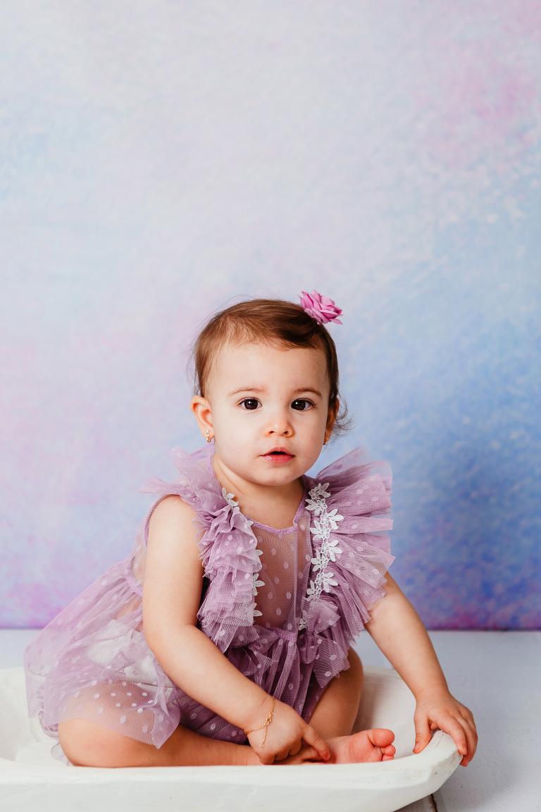 Image d'une petite fille de 17 mois en tenue violette devant un fond violet