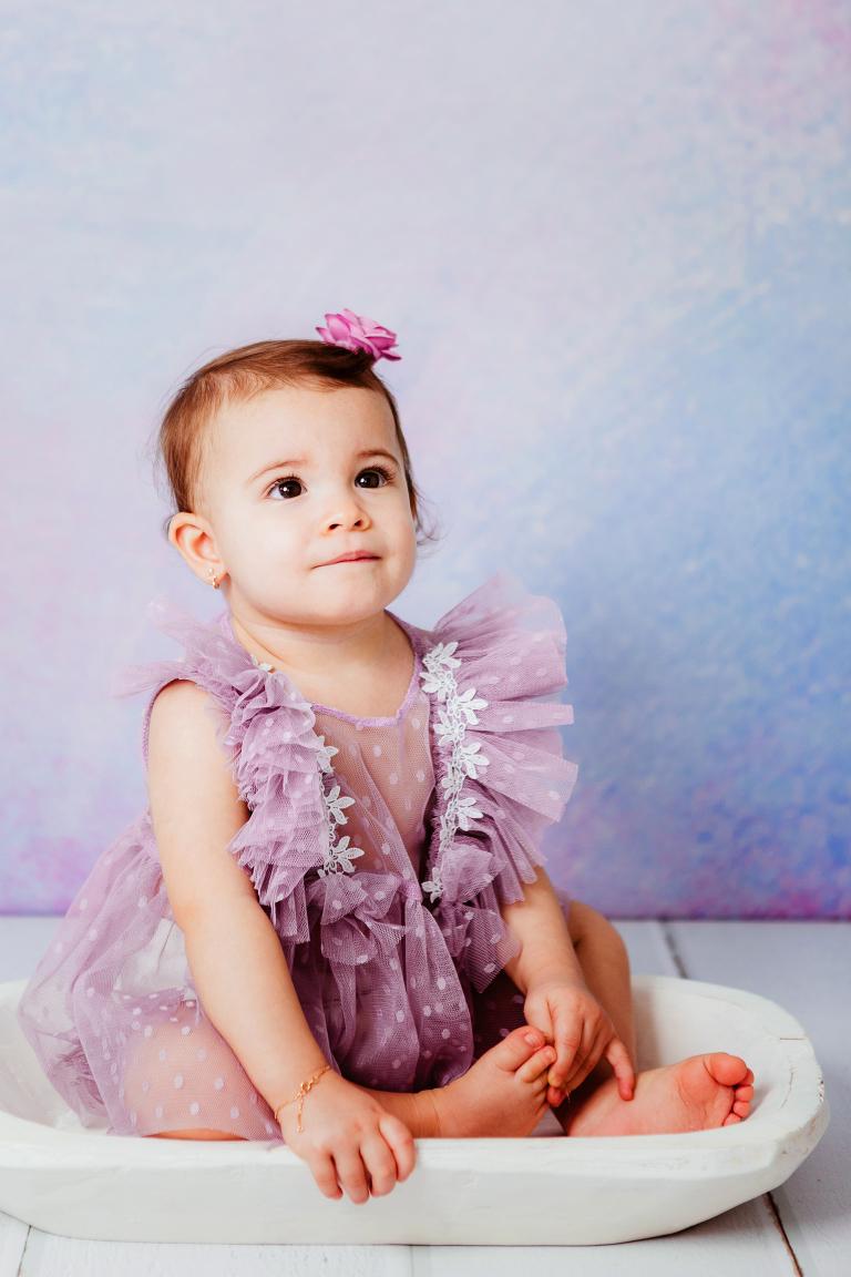 Image d'une petite fille de 17 mois en tenue violette assise dans un bol